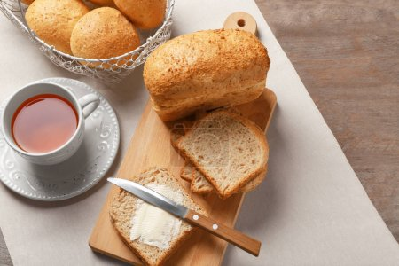 Beautiful composition with delicious bread and cup of tea on wooden table