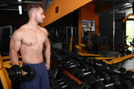 Sporty young man doing exercise with dumbbell in g...
