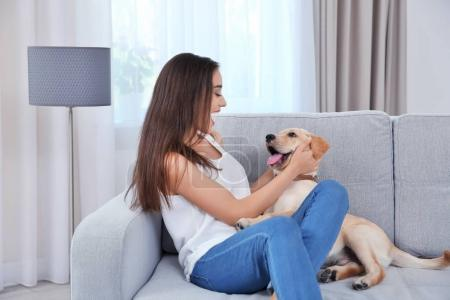 Young woman resting with yellow retriever at home