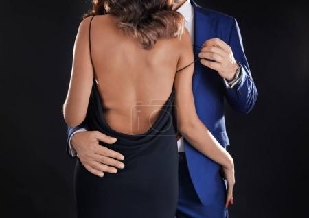 Photo for Man in formal suit undressing woman on black background - Royalty Free Image