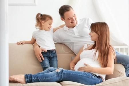 Happy young family on sofa at home