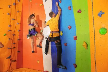 Young couple exercising in climbing gym...