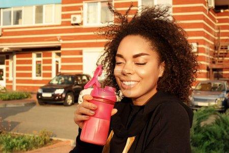Beautiful Afro American woman drinking protein sha...