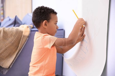 Little African-American boy drawing on paper roller indoors