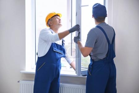 Photo for Construction worker with trainee installing window in house - Royalty Free Image