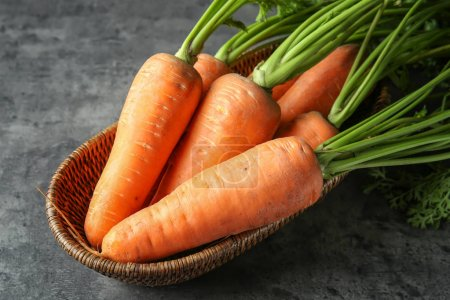 Photo for Wicker bowl with ripe carrots on table - Royalty Free Image