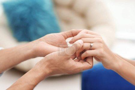 L'homme de main du holding fiancée avec bague de fiançailles sur fond flou