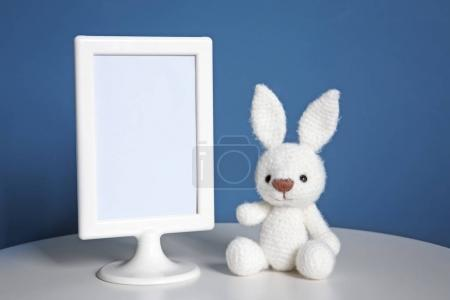 Mockup of blank frame with toy on color background