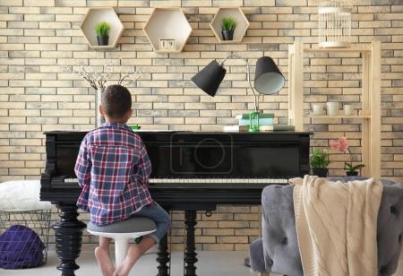 Foto de Niño afroamericano tocando el piano en el interior - Imagen libre de derechos