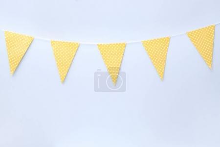 Handmade yellow garland on light wall