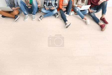 Group of teenagers with modern devices sitting on floor