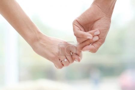 Man holding fiancee's hand with engagement ring on blurred background