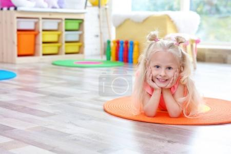 Cute little girl lying on floor at home