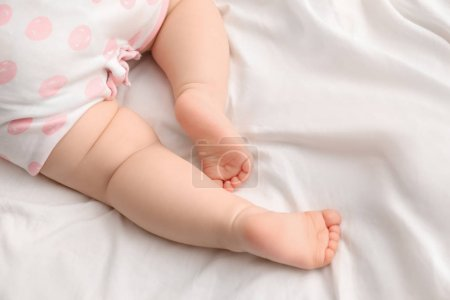 Cute little baby on bed, closeup of legs