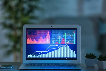 Monitor of laptop with stock data on table