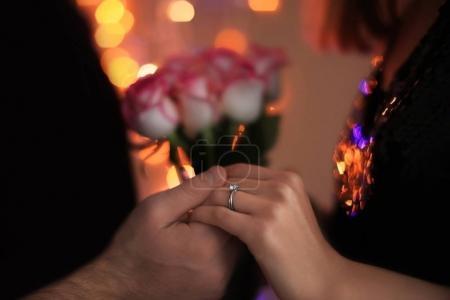 Man holding fiancee's hand with engagement ring against blurred lights