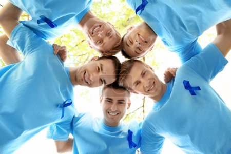Young men in t-shirts with with blue ribbons holding their heads together in circle outdoors. Prostate cancer awareness concept