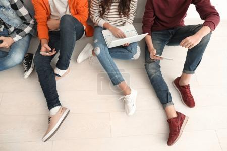 Foto de Grupo de adolescentes con los dispositivos modernos sentado en el piso - Imagen libre de derechos