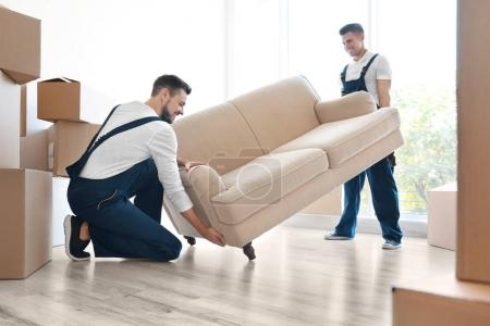 Photo for Delivery men moving sofa in room at new home - Royalty Free Image