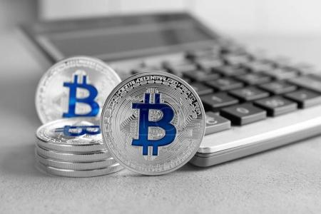 Silver bitcoins with calculator on grey background