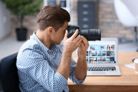 Young professional photographer taking photo in office