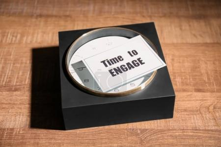Clock and card with phrase TIME TO ENGAGE on wooden background