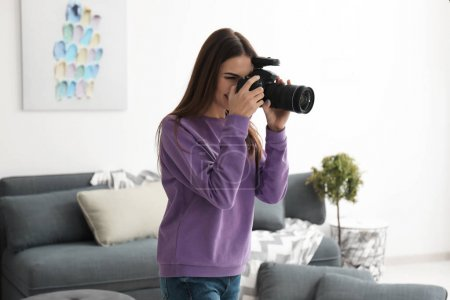 Young female photographer indoors