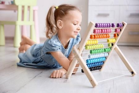 Cute little girl playing with counting frame at home