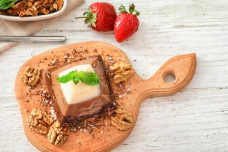 Yummy dessert with caramel and nuts on wooden board