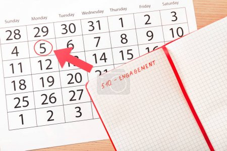 Calendar and notebook with written word ENGAGEMENT on wooden background