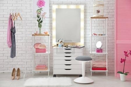 View of makeup room with decorative cosmetics and tools on dressing table