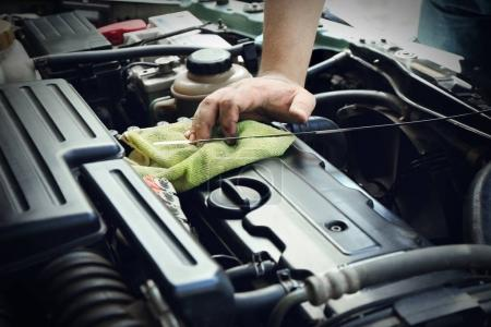 Auto mechanic checking engine oil level in body shop