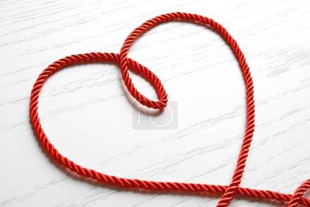 Coeur de corde rouge sur un fond en bois blanc