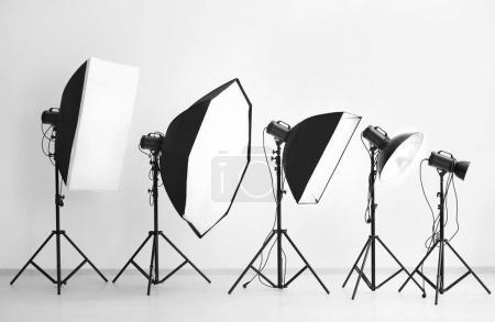 Photo pour Équipement de foudre près du mur blanc dans le studio de photo - image libre de droit