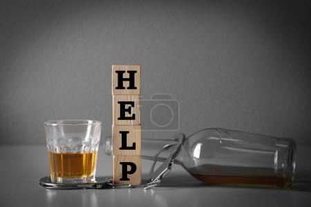Strong drink, handcuffs and cubes with word HELP on table. Concept of alcoholism