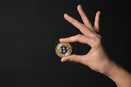 Female hand with golden bitcoin on dark background
