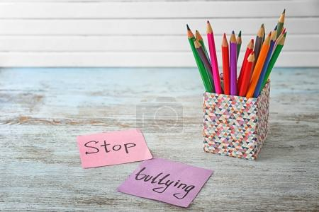 """Notes with text """"Stop bullying"""" and pencil holder on table"""
