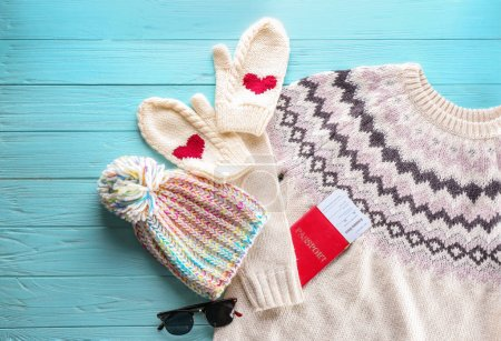 Photo for Warm clothes with documents on wooden background. Winter vacation concept - Royalty Free Image