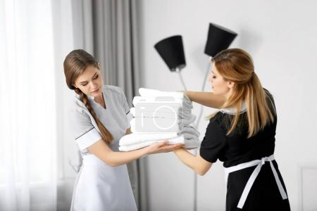 Chambermaid in uniform teaching trainee indoors...