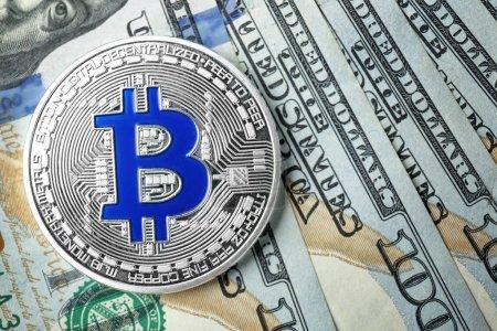 Silver bitcoin on dollar bills