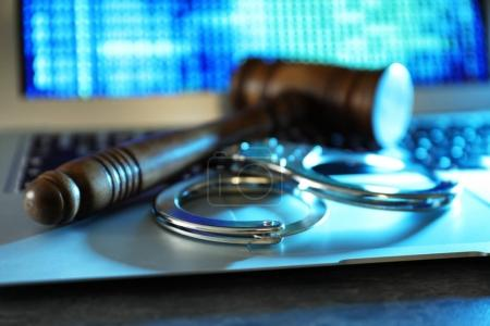 Judge gavel and handcuffs on laptop