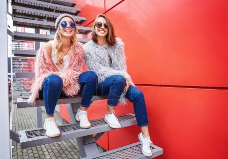 Two happy hipster girls sitting on stairs outdoors