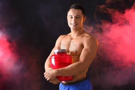 young man with jar of protein powder