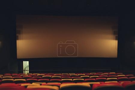 Empty cinema with large screen and comfortable chairs