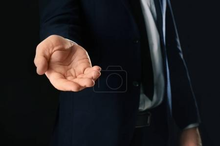 Photo for Businessman demanding bribe on black background - Royalty Free Image