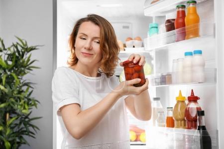Beautiful woman opening jar with tomatoes near refrigerator