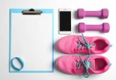 Clipboard with blank paper for exercise plan, gym stuff and mobile phone on white background. Flat lay composition