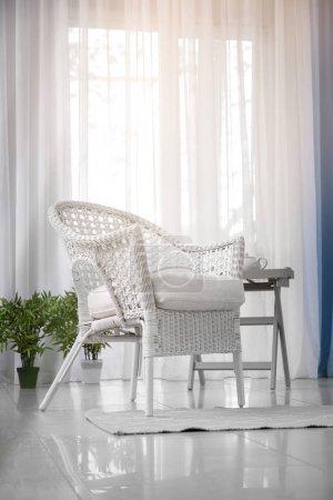 Elegant living room interior with comfortable wicker armchair