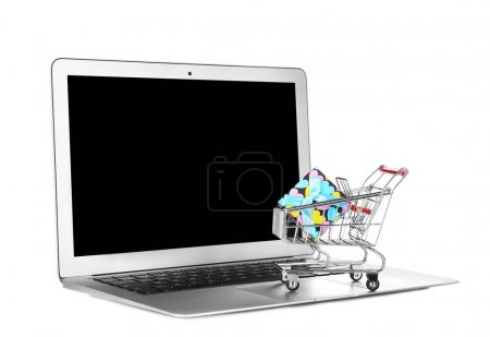 Laptop and small cart with gift box on white background. Internet shopping concept