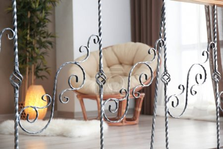 Elegant living room interior with comfortable armchair, view through decorative railing